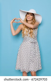 Beautiful young woman in white dotted summer dress and sun hat is showing heart shape hand sign, looking away and smiling. Three quarter length studio shot on blue background.