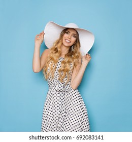 Beautiful young woman in white dotted summer dress and sun hat is smiling and looking at camera. Three quarter length studio shot on turquoise background.