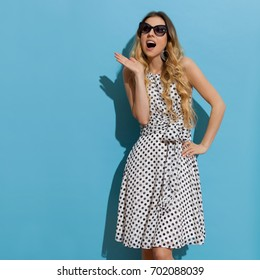 Beautiful young woman in white dotted summer dress and sunglasses is looking away and shouting. Three quarter length studio shot on turquoise background.