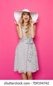Beautiful young woman in white dotted summer dress and sun hat is standing with hands raised, shouting and looking at camera. Three quarter length studio shot on pink background.