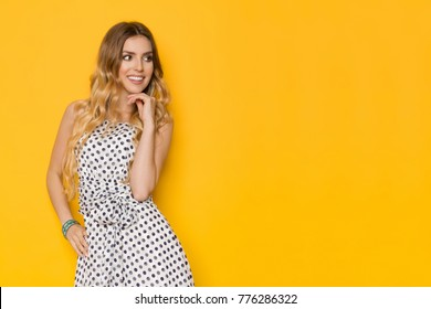 Beautiful young woman in white dotted summer dress is holding hand on chin, looking away and smiling. Three quarter length studio shot on yellow background.