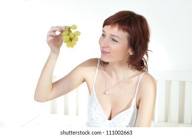 Beautiful young woman in a white dress with fruit