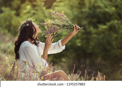 Beautiful young woman in white dress smelling wild flowers at the rural sunny landscape background in summer. Portrait of natural beauty model with curly hair and wreath outdoor sitting in freedom