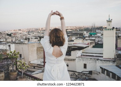 Beautiful young woman in white dress looking to the view of Fez city from terrace. Woman raising arms and stretching her body. Amazing view of old medina during sunset. Mosque in background. MOROCCO.
