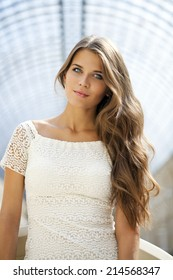 Beautiful young woman in white dress, indoor