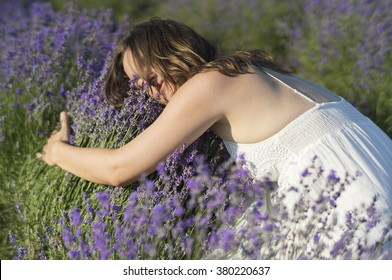 Beautiful young woman with a white dress hugging a lavender bush enjoying the fragrance.