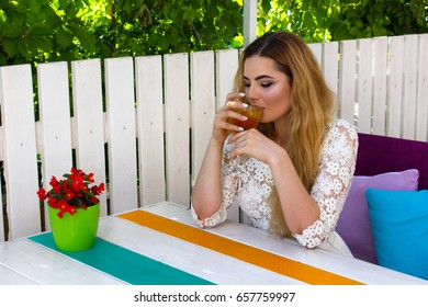 Beautiful young woman in white dress drinking cocktail in the restaurant during summer