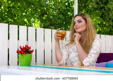 Beautiful young woman in white dress sitting in the restaurant with a drink during summer