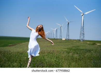Beautiful young woman in white dress in the floor by the windmills.