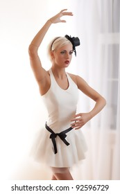 Beautiful young woman in white dress with small hat and black belt is acting as a living doll in a white empty room.
