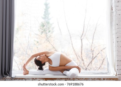 Beautiful young woman in white gymnastic suit doing an exercise for stretching back and legs sitting on the window sill of large window