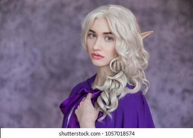 Beautiful young woman with white hair, on a purple background in a raincoat. Medieval fantasy costume. The heroine of a fairy tale elf, princess, fairy.