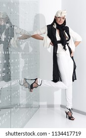 Beautiful young woman in white hat, high heels and white suit is standing, looking in camera. Full length studio shot on white background.