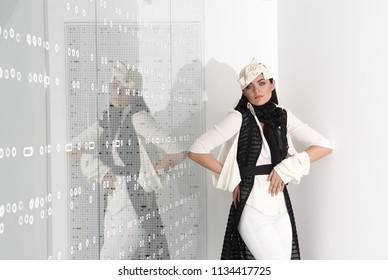 Beautiful young woman in white hat, high heels and white suit is standing, looking in camera. Studio shot on white background.