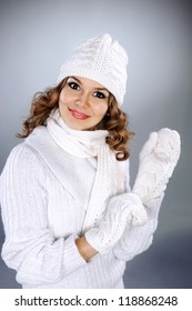 Beautiful young woman in white knitted sweater, scarf, hat and gloves