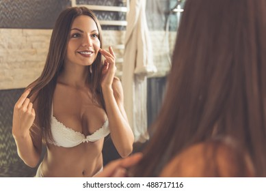 Beautiful young woman in white lingerie is touching her face and smiling while looking into the mirror in bathroom