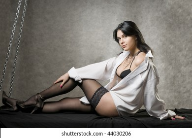 Beautiful young woman in a white man's shirt and black stockings.