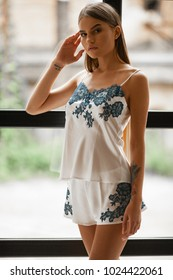 Beautiful young woman in white pajamas with blue lace flower tracery stands against background of window. Closeup.