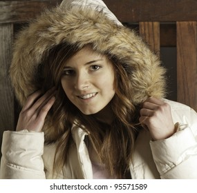 Beautiful young woman in white parka warms up after being outdoors.