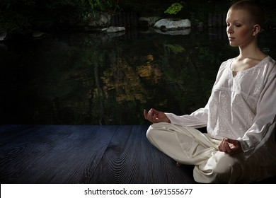 Beautiful young woman in white robe sits in meditation on the background of the zen garden..Meditation is the best way to solve the most complex problems.