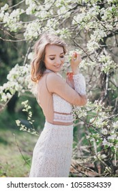 Beautiful young woman in a white romantic dress posing near blooming tree