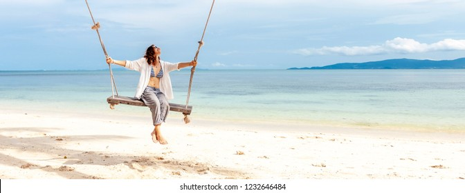 Beautiful young woman in a white shirt swinging on a swing on the beach, against the backdrop of a paradise landscape with turquoise water