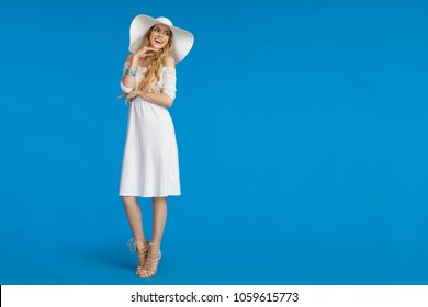 Beautiful young woman in white summer dress, high heels and sun hat is standing,  looking away and smiling. Full length studio shot on blue background.
