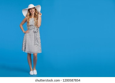 Beautiful young woman in white summer dress, sneakers and sun hat is standing, looking at camera and talking. Full length studio shot on blue background.