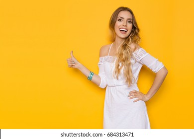 934c766cf213 Beautiful young woman in white summer dress is showing thumb up