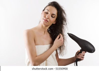 beautiful young woman with white towel and wet hair holding blow dryer