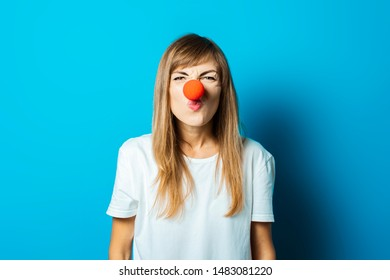 Beautiful young woman in a white t-shirt and red nose of a clown makes a grimace on a blue background. Concept party, costume, red nose day