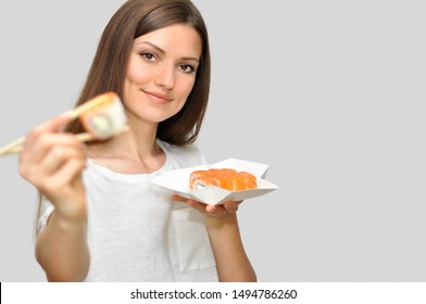 A beautiful young woman in a white T-shirt is smiling and holding a box of rolls of food delivery.Woman holds sushi with chopsticks and shows roll close.