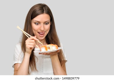 A beautiful young woman in a white T-shirt holding a box of rolls of food delivery.A young woman looks at sushi rolls and licks her lips.
