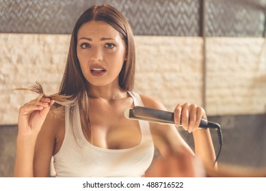 Beautiful young woman in white undershirt is looking at camera and holding her damaged hair while using a hair straightener, standing in front of the mirror in the bathroom