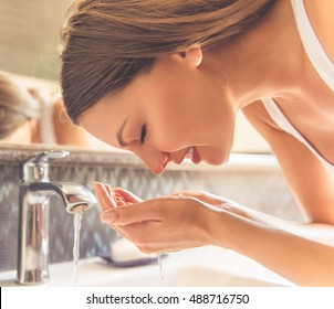 Beautiful young woman in white undershirt is washing her face and smiling while standing in front of the mirror in the bathroom