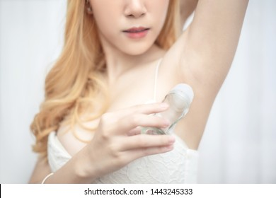 Beautiful young woman in white underwear applying roll on deodorant on her underarm
