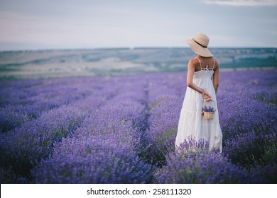 Beautiful young woman in wicker hat and white dress posing in a lavender field with small wicker basket in her hand