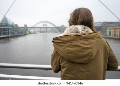 Beautiful young woman in a winter jacket, with brown hair and brown eyes, leaning on the railings of Gateshead Millenium Bridge, looking away.  Tyne Bridge and Sage Gateshead behind her.