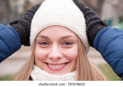Beautiful young woman in winter jacket, knitted beanie hat and scarf