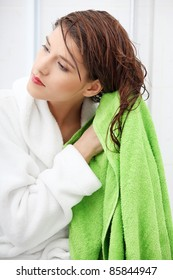 Beautiful young woman wipes her hairs with a towel.