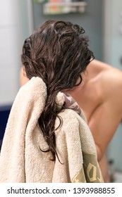 Beautiful young woman wiping hair with towel after shower. vertical photo