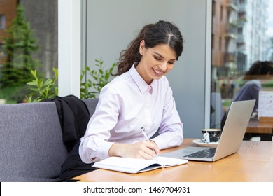 Beautiful young woman work in caffe. Woman writing and using laptop while sitting in restaurant