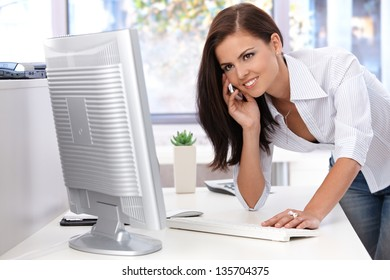 Beautiful young woman working in bright office, using mobile, smiling.