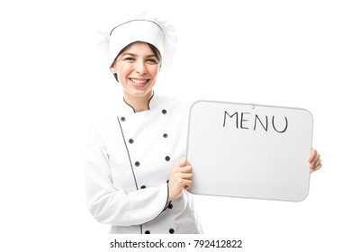 Beautiful young woman working as a chef and showing the menu for the day with a smile