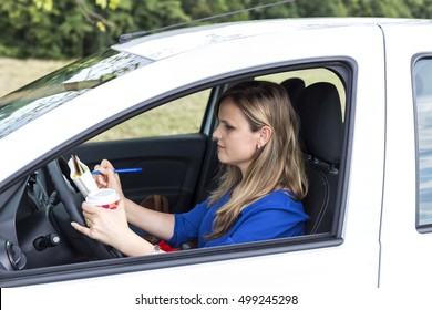 Beautiful young woman working and drinking coffee while driving