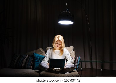 beautiful young woman working in the evening at a laptop sitting on the couch