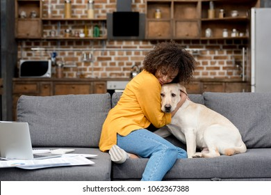 beautiful young woman working at home and cuddling with her dog
