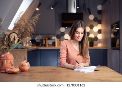 Beautiful young woman working at home in a warm, cozy environment, writing in a notebook