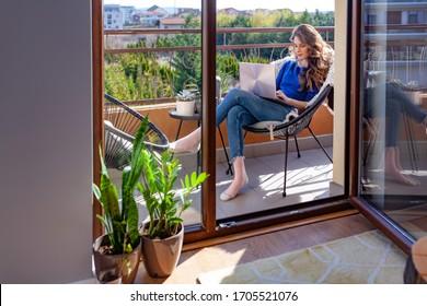 Schöne junge Frau, die von zu Hause auf dem Balkon auf ihrem Laptop arbeitet
