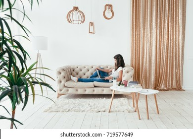 Beautiful young woman working from home on a laptop lying on the sofa in the room
